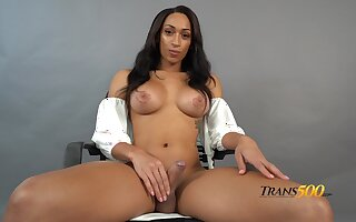 Tanned busty shemale Jasmin Lotus gets nude and wanks herself